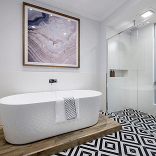Design ideas for a large contemporary master bathroom in Perth with flat-panel cabinets, black cabinets, a freestanding tub, a double shower, white tile, white walls, porcelain floors, engineered quartz benchtops, a hinged shower door and black floor.