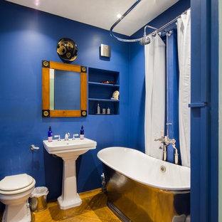 Ispirazione per una stanza da bagno per bambini minimalista di medie dimensioni con vasca freestanding, vasca/doccia, pareti blu, doccia con tenda, nessun'anta, ante blu, WC monopezzo, parquet scuro, lavabo a colonna e pavimento marrone