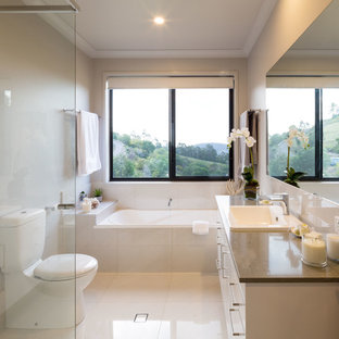 This is an example of a contemporary master bathroom in Brisbane with flat-panel cabinets, white cabinets, an alcove tub, a corner shower, a one-piece toilet, beige tile, beige walls, a drop-in sink, beige floor, an open shower and brown benchtops.