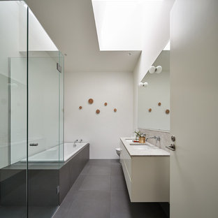 Design ideas for a contemporary master bathroom in Melbourne with flat-panel cabinets, white cabinets, a drop-in tub, white walls, an undermount sink and grey floor.