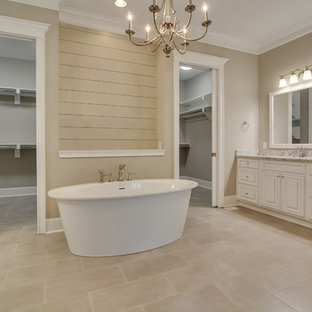 Large country master beige tile and porcelain tile porcelain floor and beige floor bathroom photo in Atlanta with raised-panel cabinets, white cabinets, a one-piece toilet, gray walls, a drop-in sink and granite countertops