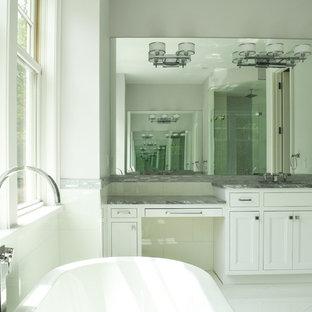 Diseño de cuarto de baño principal, marinero, extra grande, con armarios con paneles empotrados, puertas de armario blancas, bañera exenta, ducha empotrada, sanitario de pared, baldosas y/o azulejos blancos, paredes blancas, suelo de mármol, lavabo bajoencimera y encimera de mármol