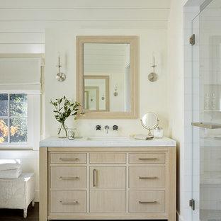 Foto di una stanza da bagno country con consolle stile comò, ante in legno chiaro, doccia alcova, pareti bianche, parquet scuro, lavabo sottopiano, pavimento marrone, porta doccia a battente e top bianco