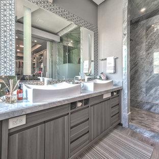 Immagine di una stanza da bagno di medie dimensioni con ante grigie, piastrelle grigie, piastrelle di marmo, pavimento in linoleum, top in marmo e pavimento beige