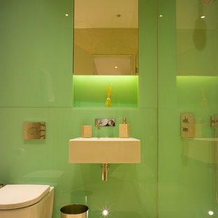 Foto de cuarto de baño con ducha, contemporáneo, de tamaño medio, con ducha abierta, sanitario de pared, baldosas y/o azulejos verdes, baldosas y/o azulejos de vidrio, paredes verdes, suelo vinílico y lavabo suspendido