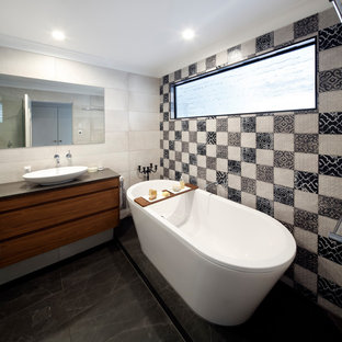 Design ideas for a mid-sized mediterranean master bathroom in Sydney with flat-panel cabinets, medium wood cabinets, a freestanding tub, beige tile, black and white tile, cement tile, a vessel sink, black floor, brown benchtops, a corner shower, a one-piece toilet, grey walls, porcelain floors, engineered quartz benchtops and a hinged shower door.