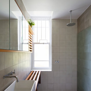 This is an example of a contemporary wet room bathroom in Sydney with open cabinets, medium wood cabinets, beige tile, gray tile, cement tile, grey walls, cement tiles, a vessel sink, wood benchtops, grey floor, an open shower and brown benchtops.