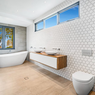 Design ideas for a large contemporary 3/4 bathroom in Wollongong with flat-panel cabinets, medium wood cabinets, a freestanding tub, a wall-mount toilet, white tile, a vessel sink, wood benchtops, beige floor and brown benchtops.