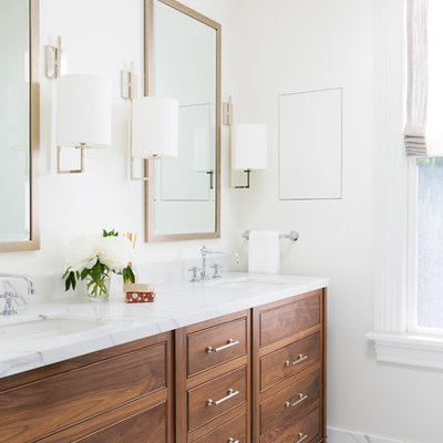 Inspiration for a timeless white floor bathroom remodel in San Francisco with beaded inset cabinets, medium tone wood cabinets, white walls, an undermount sink and white countertops