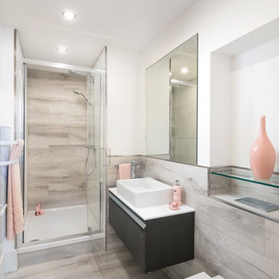 Photo of a contemporary shower room in Manchester with flat-panel cabinets, black cabinets, an alcove shower, a wall mounted toilet, grey tiles, a trough sink, grey floors and a hinged door.