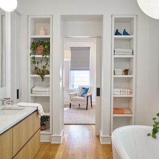 Diseño de cuarto de baño principal, clásico renovado, con armarios con paneles lisos, puertas de armario de madera oscura, bañera exenta, paredes blancas, suelo de madera en tonos medios, lavabo bajoencimera, suelo marrón y encimeras blancas