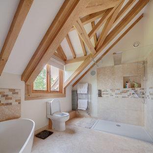 Foto på ett lantligt en-suite badrum, med ett fristående badkar, en hörndusch, en toalettstol med separat cisternkåpa, beige kakel, brun kakel, vita väggar och beiget golv
