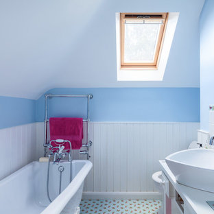 Design ideas for a rural bathroom in Surrey with white cabinets, a freestanding bath, white tiles, blue walls, a vessel sink and multi-coloured floors.