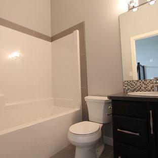 Foto på ett litet amerikanskt badrum, med ett nedsänkt handfat, släta luckor, skåp i mörkt trä, laminatbänkskiva, ett badkar i en alkov, en dusch/badkar-kombination, en toalettstol med hel cisternkåpa, grå kakel, mosaik, grå väggar och klinkergolv i keramik