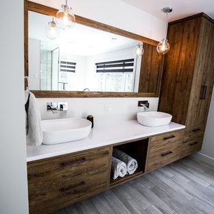 Diseño de cuarto de baño principal, rústico, grande, con armarios con paneles lisos, puertas de armario de madera oscura, bañera exenta, ducha esquinera, baldosas y/o azulejos blancas y negros, baldosas y/o azulejos de porcelana, paredes grises, suelo de baldosas de porcelana, lavabo sobreencimera y encimera de laminado