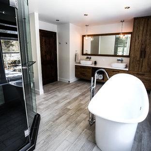 Imagen de cuarto de baño principal, rural, grande, con armarios con paneles lisos, puertas de armario de madera oscura, bañera exenta, ducha esquinera, baldosas y/o azulejos blancas y negros, baldosas y/o azulejos de porcelana, paredes grises, suelo de baldosas de porcelana, lavabo sobreencimera y encimera de laminado