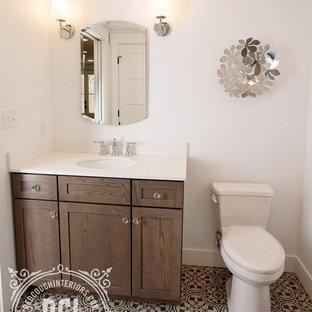 Ejemplo de cuarto de baño con ducha, campestre, de tamaño medio, con armarios estilo shaker, puertas de armario marrones, ducha empotrada, sanitario de una pieza, paredes blancas, suelo de linóleo, lavabo bajoencimera, encimera de cuarzo compacto, suelo negro y ducha con cortina