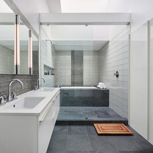 Ispirazione per una grande stanza da bagno padronale design con ante lisce, ante bianche, vasca sottopiano, doccia aperta, piastrelle bianche, piastrelle di vetro, pareti bianche, lavabo sottopiano e pavimento grigio