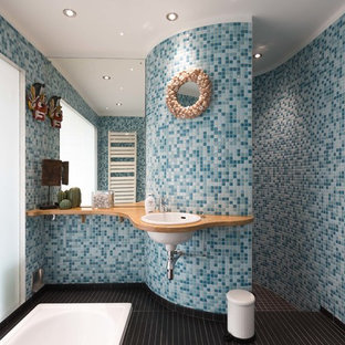 Photo of a medium sized contemporary ensuite bathroom in London with blue tiles, mosaic tiles, blue walls, ceramic flooring, wooden worktops, black floors, beige worktops and a built-in sink.