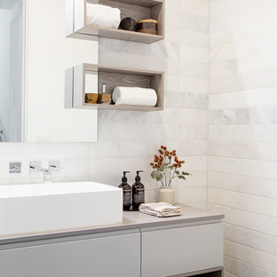 Inspiration for a contemporary white tile and marble tile dark wood floor and brown floor bathroom remodel in Los Angeles with flat-panel cabinets, gray cabinets, a wall-mount toilet, white walls, a vessel sink and gray countertops