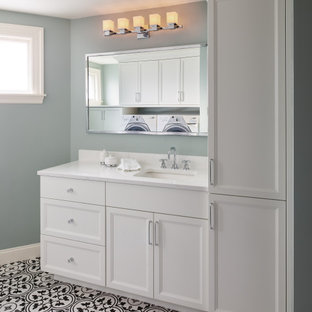 Example of a mid-sized transitional mosaic tile floor, multicolored floor and single-sink bathroom/laundry room design in Boston with recessed-panel cabinets, white cabinets, an undermount sink, white countertops, a built-in vanity and blue walls