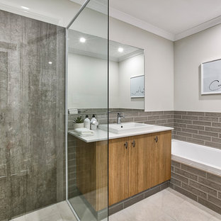 Inspiration for a mid-sized contemporary master bathroom in Perth with a corner shower, brown tile, white walls, beige floor, a hinged shower door, white benchtops, flat-panel cabinets, medium wood cabinets, a drop-in tub and a drop-in sink.