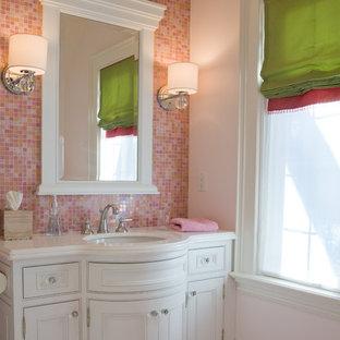 Modelo de cuarto de baño infantil, clásico, con lavabo bajoencimera, armarios con paneles empotrados, puertas de armario blancas, baldosas y/o azulejos rosa y baldosas y/o azulejos en mosaico