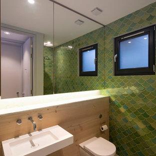 Immagine di una piccola stanza da bagno design con lavabo sospeso, vasca freestanding, pareti verdi, WC monopezzo, pavimento in cemento e piastrelle verdi