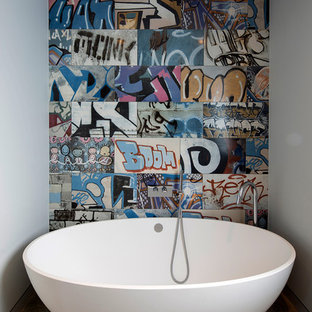 Example of a small trendy multicolored tile freestanding bathtub design in London with multicolored walls