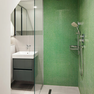 Photo of a contemporary bathroom in London with a wall-mounted sink, flat-panel cabinets, grey cabinets, a built-in shower, green tiles, mosaic tiles, green walls and grey floors.