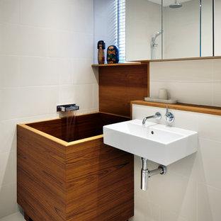 Asiatisk inredning av ett badrum, med ett väggmonterat handfat, ett japanskt badkar och beige kakel
