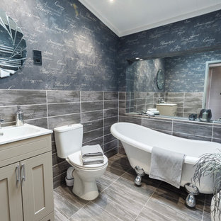 This is an example of a medium sized coastal bathroom in Other with recessed-panel cabinets, beige cabinets, a claw-foot bath, a one-piece toilet, grey tiles, grey walls, a submerged sink and grey floors.