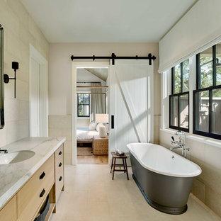 Diseño de cuarto de baño principal, campestre, con armarios con paneles lisos, puertas de armario de madera clara, bañera exenta, baldosas y/o azulejos beige, paredes beige, lavabo bajoencimera, suelo beige y encimeras blancas