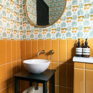 Idées déco pour une salle de bain contemporaine avec un placard sans porte, des portes de placard noires, un carrelage orange, un mur multicolore, une vasque et du papier peint.