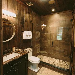 Bild på ett mellanstort rustikt badrum med dusch, med luckor med infälld panel, skåp i mörkt trä, en dusch i en alkov, en toalettstol med separat cisternkåpa, grå kakel, stenkakel, bruna väggar, travertin golv, ett undermonterad handfat och bänkskiva i täljsten