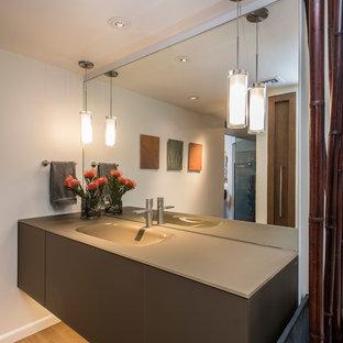 Esempio di una piccola stanza da bagno con doccia minimal con ante di vetro, ante grigie, piastrelle bianche, pareti beige, pavimento in legno massello medio, lavabo sospeso, top in cemento e pavimento beige
