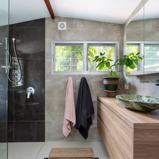 This is an example of a contemporary bathroom in Sunshine Coast with flat-panel cabinets, medium wood cabinets, a curbless shower, gray tile, a vessel sink, wood benchtops, beige floor, an open shower, brown benchtops, a single vanity, a floating vanity and vaulted.