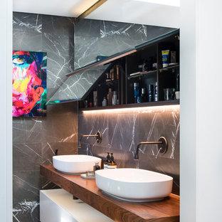 Стильный дизайн: маленькая главная ванная комната в современном стиле с фасадами островного типа, белыми фасадами, открытым душем, инсталляцией, серой плиткой, каменной плиткой, серыми стенами, светлым паркетным полом, настольной раковиной, столешницей из дерева, открытым душем, бежевым полом и коричневой столешницей - последний тренд