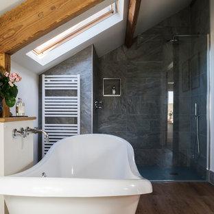 Diseño de cuarto de baño principal, de estilo de casa de campo, grande, con bañera exenta, ducha abierta, baldosas y/o azulejos grises, baldosas y/o azulejos de piedra, paredes blancas, lavabo sobreencimera, encimera de mármol, suelo marrón, ducha con puerta corredera y suelo de madera oscura