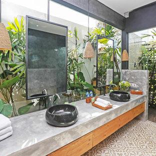 Immagine di una stanza da bagno tropicale con ante lisce, ante in legno scuro, doccia a filo pavimento, lavabo a bacinella, top in cemento, pavimento beige, doccia aperta e top grigio