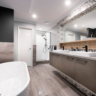 This is an example of a beach style master bathroom in Perth with flat-panel cabinets, brown cabinets, a freestanding tub, an alcove shower, multi-coloured walls, a vessel sink, a hinged shower door and grey benchtops.