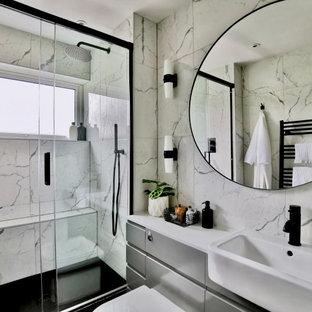 Kleines Modernes Duschbad mit flächenbündigen Schrankfronten, grauen Schränken, bodengleicher Dusche, Toilette mit Aufsatzspülkasten, weißen Fliesen, Keramikfliesen, weißer Wandfarbe, Porzellan-Bodenfliesen, integriertem Waschbecken, schwarzem Boden, Schiebetür-Duschabtrennung, weißer Waschtischplatte, Einzelwaschbecken und eingebautem Waschtisch in Sonstige