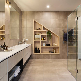 Design ideas for a large contemporary master bathroom in Melbourne with flat-panel cabinets, ceramic tile, ceramic floors, a hinged shower door, white benchtops, light wood cabinets, a curbless shower, beige tile, beige walls and beige floor.