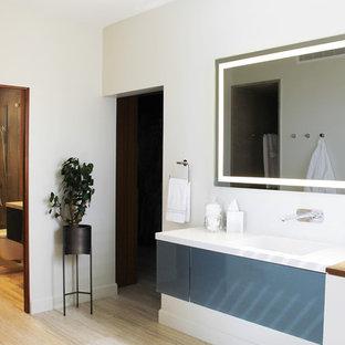Esempio di una stanza da bagno padronale moderna di medie dimensioni con ante di vetro, ante blu, doccia a filo pavimento, WC sospeso, piastrelle di cemento, pareti bianche, pavimento in travertino, lavabo sottopiano, top in quarzite, pavimento beige e porta doccia a battente