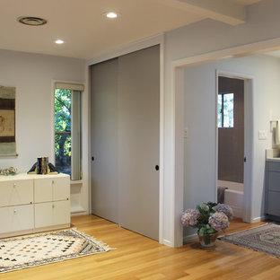 Diseño de cuarto de baño infantil, asiático, con armarios con paneles lisos, puertas de armario grises, bañera empotrada, combinación de ducha y bañera, sanitario de una pieza, baldosas y/o azulejos grises, baldosas y/o azulejos de porcelana, paredes azules, suelo de bambú, lavabo bajoencimera, encimera de cuarcita y ducha con cortina