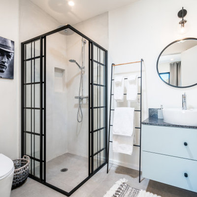 Bathroom - mid-sized industrial 3/4 gray floor and concrete floor bathroom idea in Other with flat-panel cabinets, blue cabinets, white walls, a vessel sink, gray countertops, a two-piece toilet and soapstone countertops
