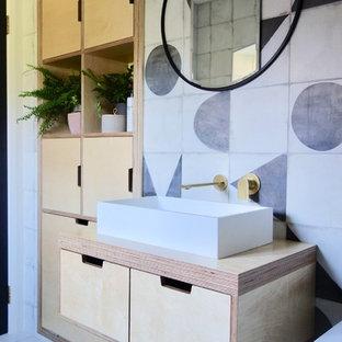 他の地域の北欧スタイルのおしゃれな子供用バスルーム (淡色木目調キャビネット、ドロップイン型浴槽、シャワー付き浴槽、一体型トイレ、モノトーンのタイル、磁器タイル、白い壁、磁器タイルの床、コンソール型シンク、木製洗面台、マルチカラーの床) の写真