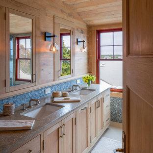 Imagen de cuarto de baño principal, rural, con lavabo bajoencimera, armarios con paneles empotrados, baldosas y/o azulejos azules, baldosas y/o azulejos de vidrio, paredes marrones, suelo de linóleo y puertas de armario de madera clara