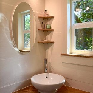 Foto på ett litet maritimt beige badrum med dusch, med öppna hyllor, beige skåp, en hörndusch, en toalettstol med hel cisternkåpa, beige kakel, keramikplattor, beige väggar, bambugolv, ett fristående handfat, träbänkskiva, beiget golv och dusch med skjutdörr