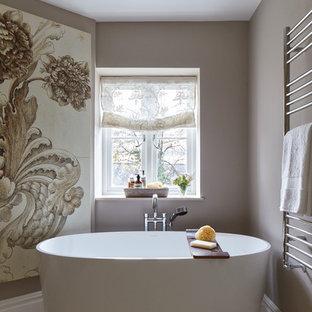 Immagine di una stanza da bagno etnica con vasca freestanding, pareti marroni e pavimento beige